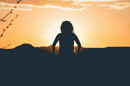 horizon silhouette of person looking at sunset oragne