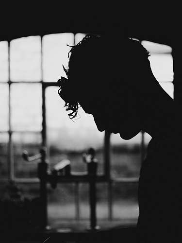 black-and-white silhouette of person near window grey