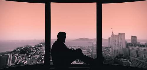 person silhouette of person sitting on building's window window
