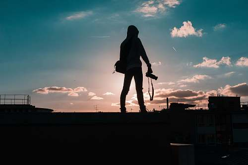 person silhouette of person standing and holding DSLR camera human