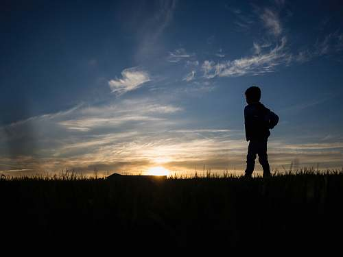 nature silhouette of person standing on grass field sky