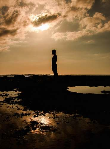 flare silhouette of person standing on rock light