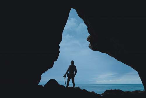person silhouette of person standing on rock blue