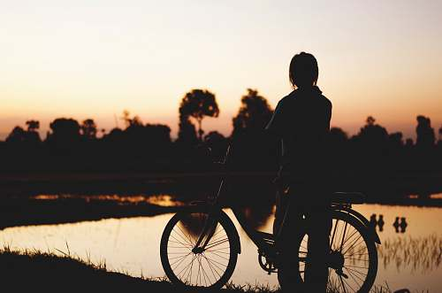person silhouette of person with bicycle near body of water bicycle