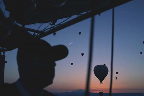 photo hot air balloon silhouette of person with hot air balloon in the air man free for commercial use images