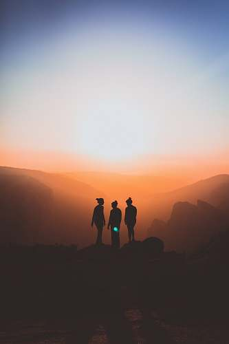woman silhouette of three people up on mountain cliff sunset