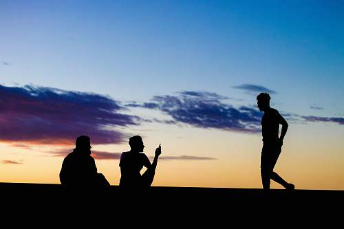 person silhouette of three persons under blue and orange skies human