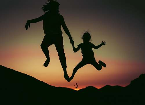 human silhouette of two children jumps person