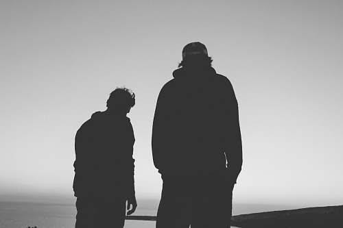 black-and-white silhouette of two man grey