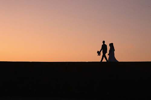 person silhouette of two people during golden hour human