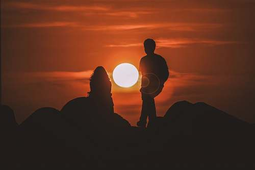 human silhouette of two people looking at sunset person