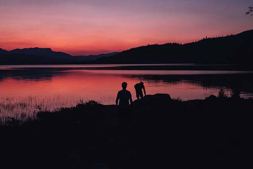 person silhouette of two people standing near body of water under orange sky nature