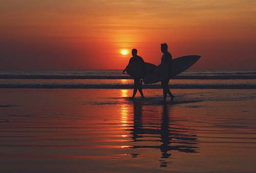 bali silhouette of two people walking on seashore during sunset indonesia
