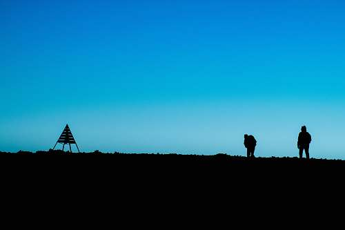 photo blue silhouette of two person standing on ground near tent at daytime morocco free for commercial use images