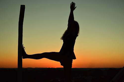 dance pose silhouette of woman doing yoga during golden hour leisure activities
