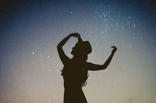 photo people silhouette of woman holding hat in blue and gray nebula woman free for commercial use images