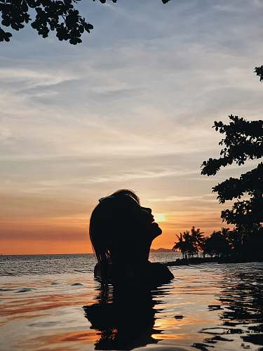 nature silhouette of woman in body of water during golden hour sunset