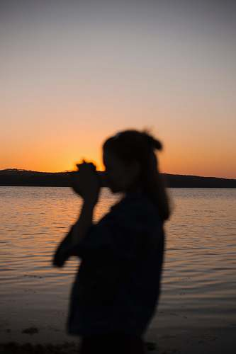 nature silhouette of woman near body of water outdoors
