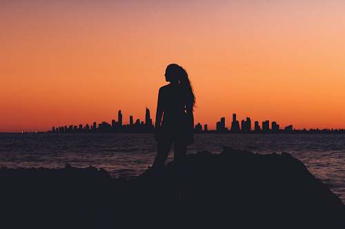 human silhouette of woman near shoreline people