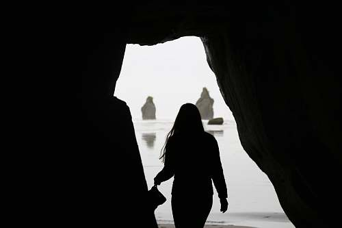 nature silhouette of woman near the cave shoreline