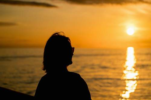 person silhouette of woman standing facing sunset human