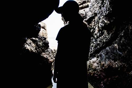 person silhouette of woman standing inside cave human