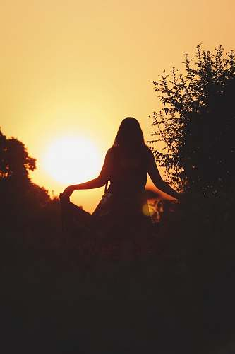 sunset silhouette of woman standing near tree sunset india