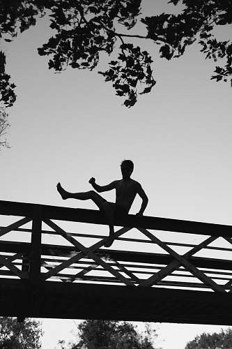 black-and-white silhouette photo of a man about to jump on footbridge cambridge