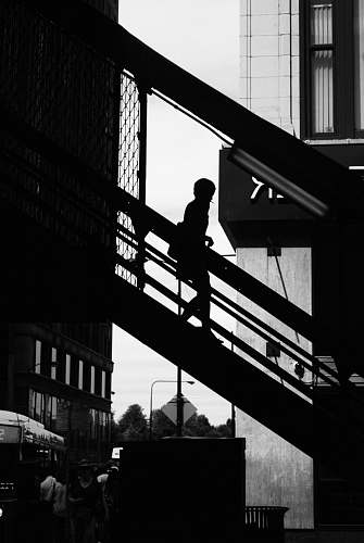 person silhouette photo of a person walking down on stair black-and-white