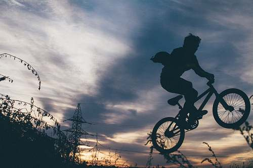 bike silhouette photo of bikers showing exhibition on air during orange sunset bmx