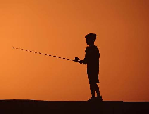 human silhouette photo of boy fishing during sunset people