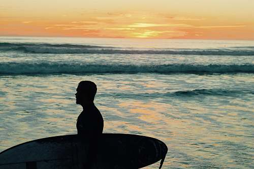 human silhouette photo of man holding surfboard person