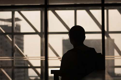 person silhouette photo of man wearing eyeglasses sitting on chair human
