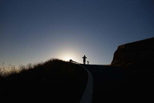 person silhouette photo of person above hill grass