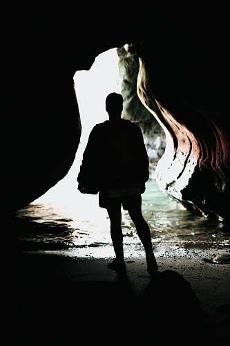 person silhouette photo of person standing in front of blue body of water inside cave during daytime people