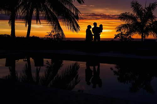 outdoors silhouette photo of three person near body of water during sunset sunset