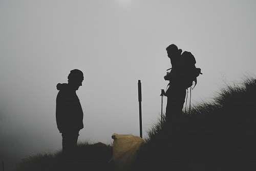 human silhouette photo of two men climbing mountain people