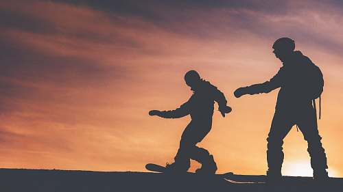person silhouette photo of two person riding on snowboard people