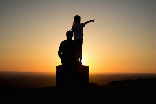 human silhouette photo of two person sitting on cliff people
