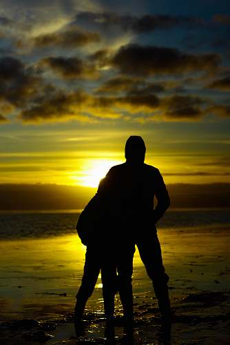 nature silhouette photo of two persons standing beside beach human