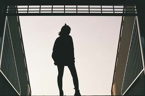 human silhouette photo of woman standing on concrete road people
