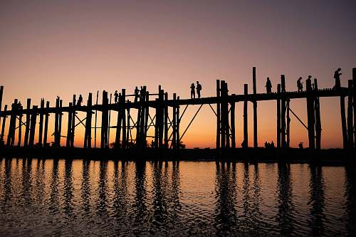 pier silhouette photograph of two person standing on wooden bridge during golden hour dock