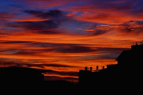 nature silhouette photography of buildings during sunset dawn