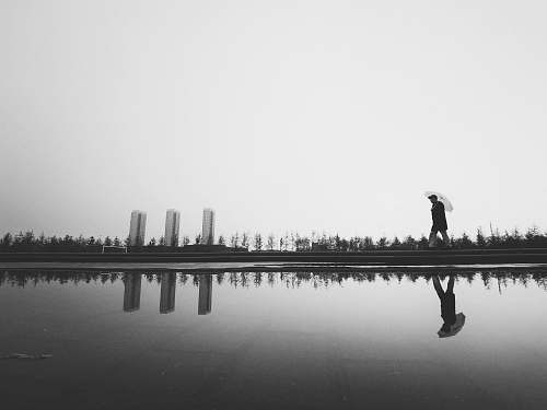 human silhouette photography of man holding umbrella beside body of water black-and-white