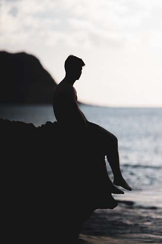human silhouette photography of man siting on a cliff nature