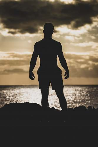 nature silhouette photography of man standing on rock formation near body of water outdoors