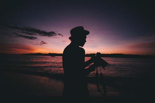 human silhouette photography of man standing while holding DSLR camera person