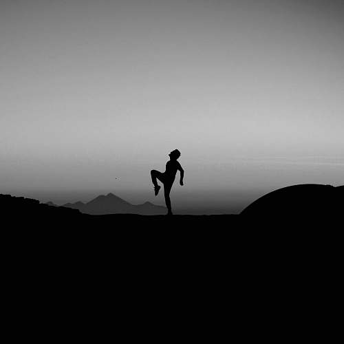 photo black-and-white silhouette photography of man standing with one leg on ground grey free for commercial use images
