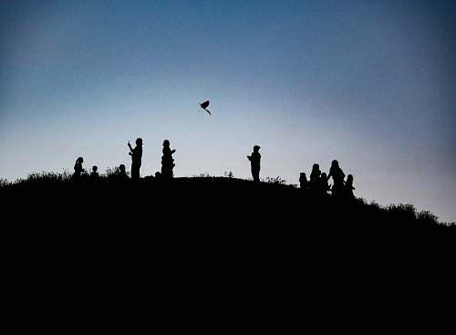 outdoors silhouette photography of people on top of a land formation animal