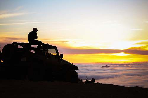human silhouette photography of person sitting on truck person
